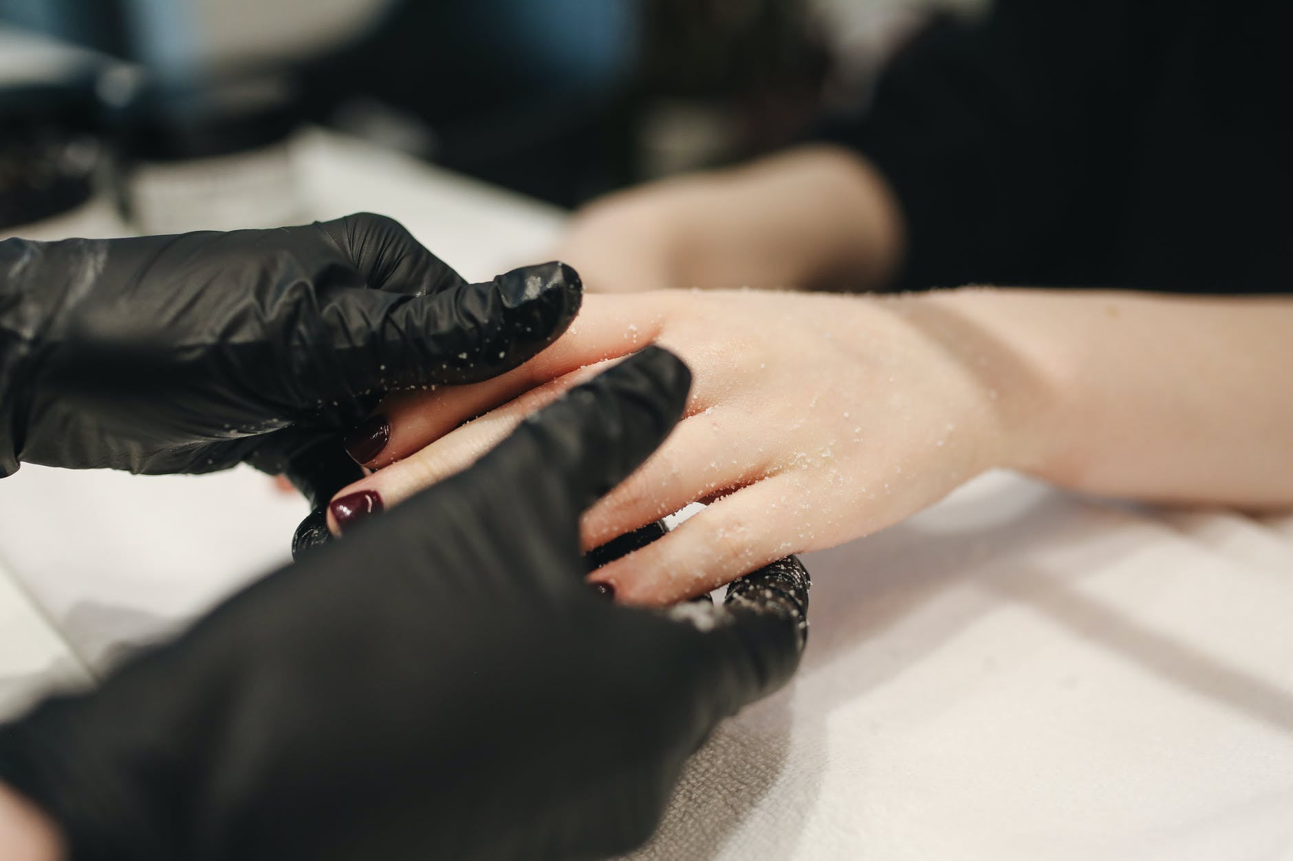 person wearing black gloves massaging a person s hand